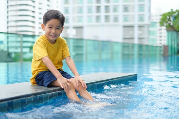 Happy asian boy sitting swimming pool