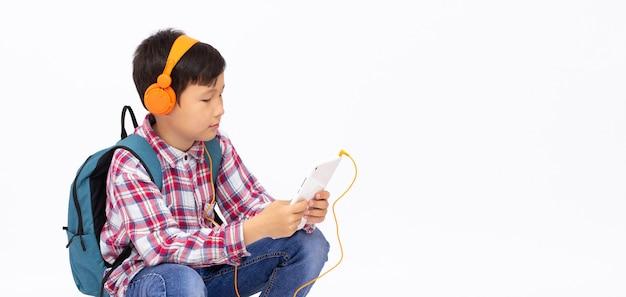 Счастливый азиатский мальчик в наушниках и играет по мобильному телефону на серой поверхности, пространство для копирования баннера с улыбкой