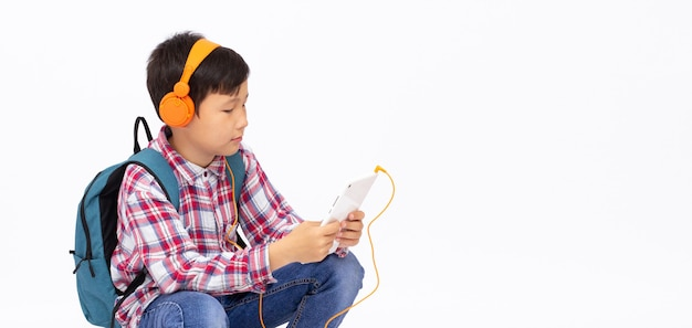 Happy asian boy ware headphone and playing the cell phone on gray surface, smile face banner copy space