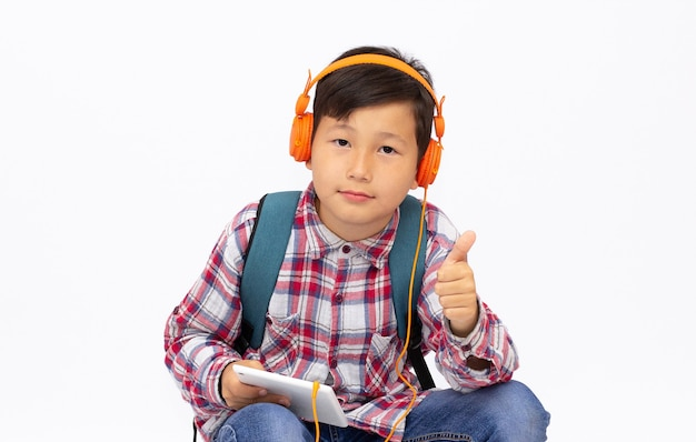 Happy asian boy ware headphone and playing the cell phone on gray surface, smile face