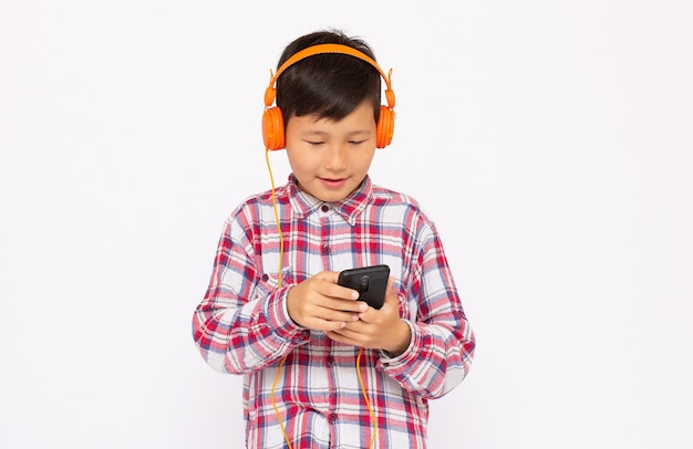 Happy asian boy wears headphone and playing the cell phone on gray surface, smile face