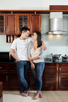 Happy asian boyfriend and girlfriend hugging and looking at each other in kitchen