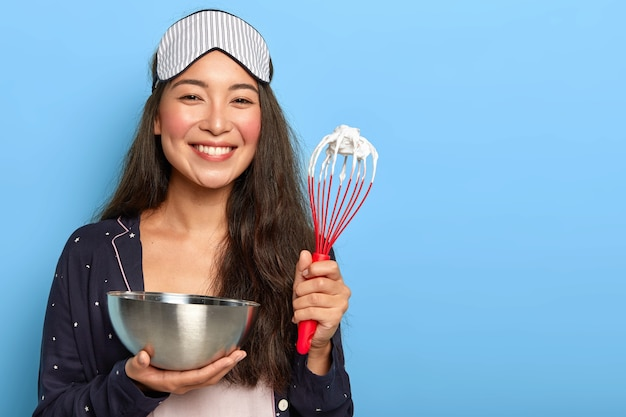Happy asian brunette woman makes delicious cake, prepares cake, whisks egg white in bowl with beater, dressed in nightwear, sleep mask