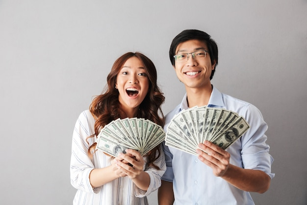 Happy asian business couple standing isolated, holding money banknotes