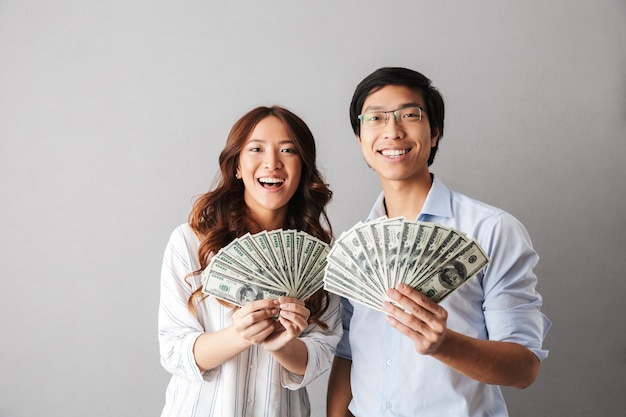 Счастливая азиатская деловая пара, стоящая изолированно, держа денежные банкноты