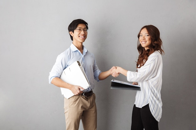 Happy asian business couple working together with documents