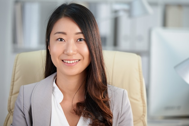 Happy asian business lady sitting in office and smiling