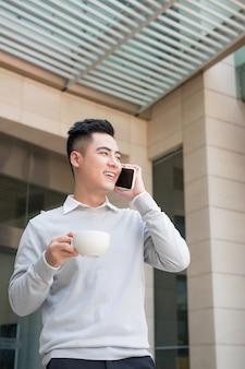 オフィスでの電話で幸せなアジアのビジネスマン