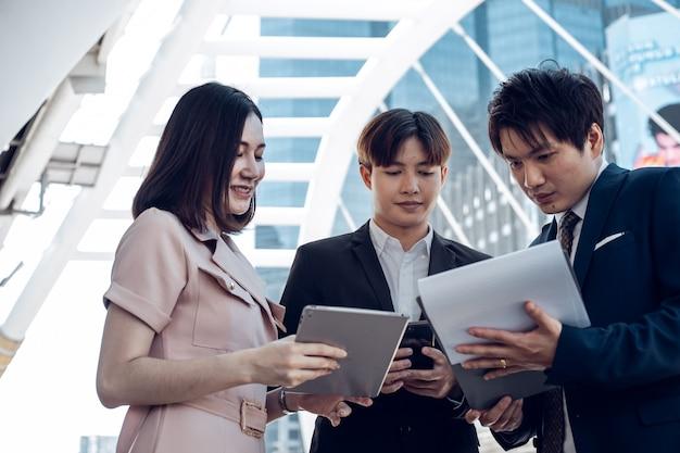 Счастливые азиатские деловые люди обсуждают успех проекта