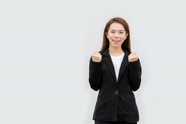 Happy asian business woman arms up in black suit isolated on white color