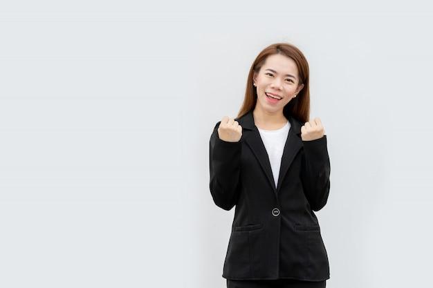 白い色に分離された黒のスーツで幸せなアジアビジネス女性の腕
