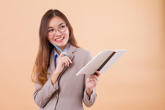 ノートを保持している幸せなアジアビジネス女性