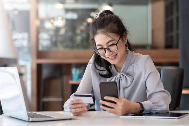 幸せなアジアのビジネス女性は、オフィスで携帯電話を使用してオンラインで支払います。