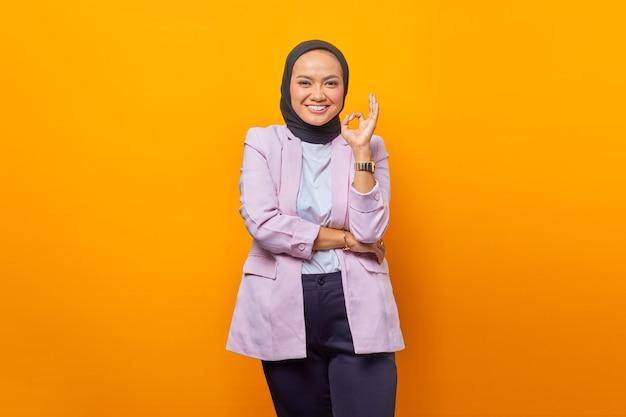 행복 한 아시아 비즈니스 여성 확인 표시를 표시 하 고 노란색 배경 위에 카메라를 보고