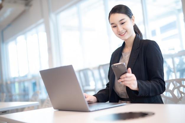 휴대 전화로 얘기 하는 행복 한 아시아 비즈니스 우먼