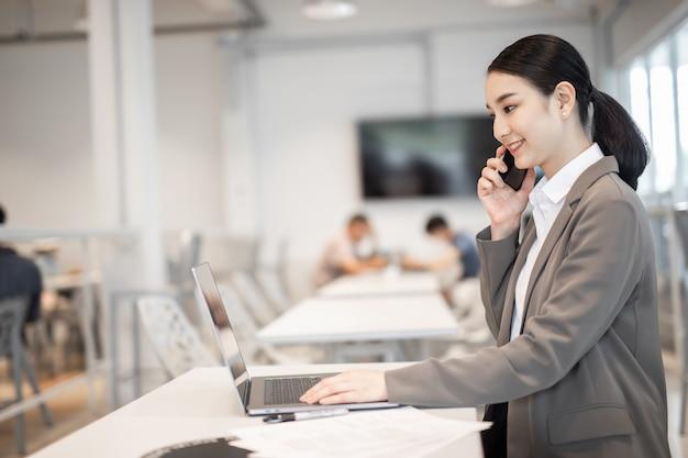 휴대 전화로 얘기 하는 행복 한 아시아 비즈니스 여자