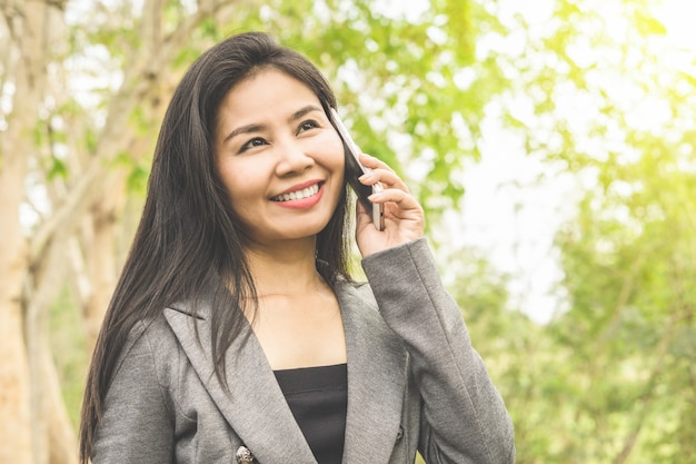 Happy asian business woman talking on  mobile phone