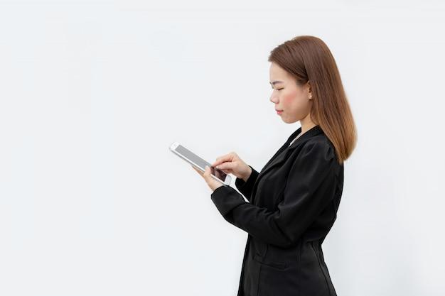 Счастливая азиатская бизнес-леди используя прибор таблетки в черном костюме изолированном на белом цвете