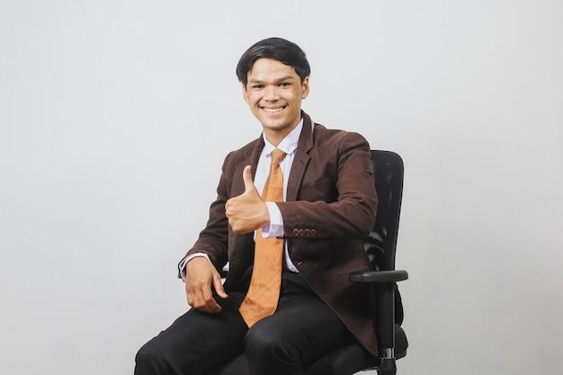Счастливый азиатский бизнесмен в пиджаке и галстуке сидит на офисном стуле и дает большой палец вверх