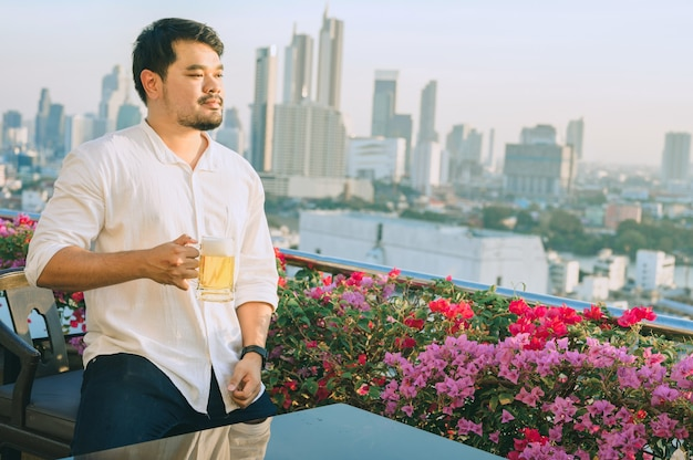 Happy asian businessman smiling while drinking beer at the rooftop restaurant
