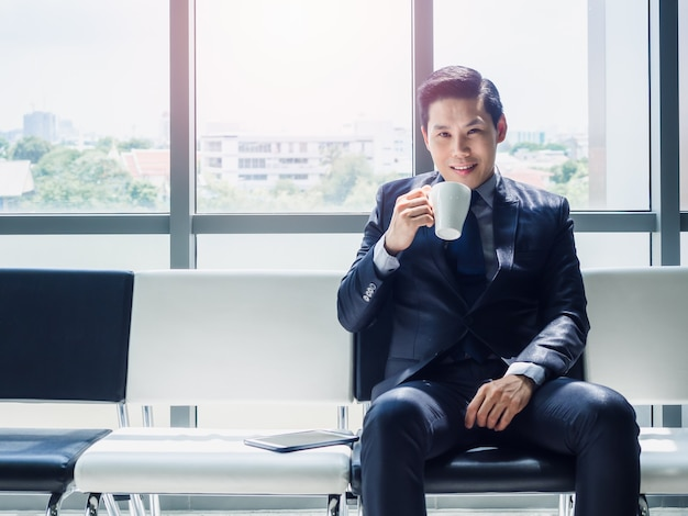 Happy asian businessman in suit drinking white cup of hot coffee while sitting on waiting chair near huge glass window with sunlight