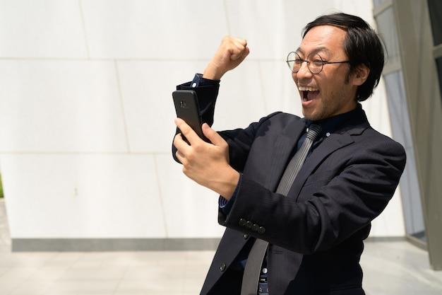 電話を使用して良いニュースを手に入れて幸せなアジアのビジネスマン