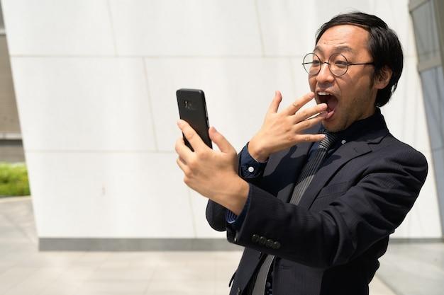 Счастливый азиатский бизнесмен с помощью телефона и выглядит удивленным outdoo