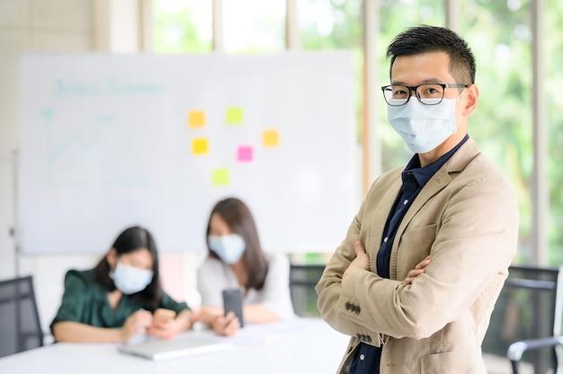 会議室でバックグラウンドで同僚と腕を組んで立っているフェイスマスクを身に着けている幸せなアジアのビジネスマン