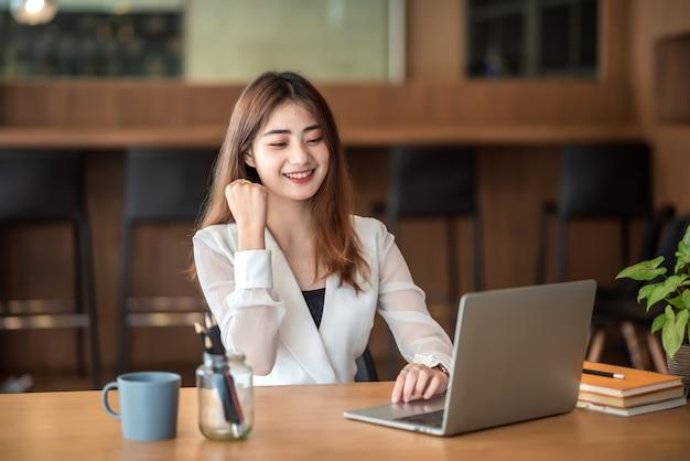 행복 한 아시아 사업가 사무실에서 노트북 앞에서 발생하는 팔으로 성공을 축 하합니다.