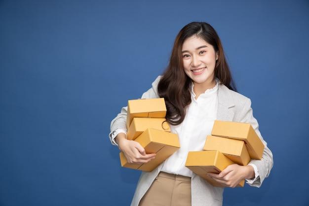 파란색 배경에 고립 된 패키지 소포 상자를 들고 행복 한 아시아 사업가