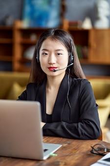 電話会議とビデオチャットで話すヘッドセットで幸せなアジアの実業家