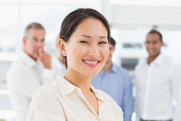 彼女の後ろにチームと一緒に立つ幸せなアジアのビジネスマン