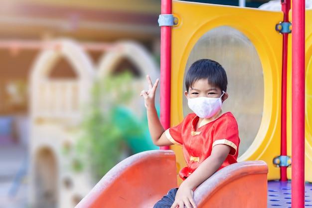 Счастливый азиатский мальчик ребенка усмехаясь и нося маску ткани, он играя с игрушкой ползунка на спортивной площадке,