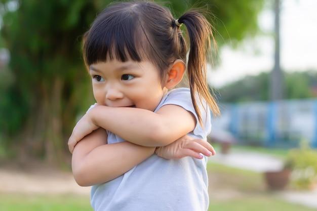 부끄러워하는 행복 한 아시아 아이. 그녀는 공원 놀이터에서 장난감을 가지고 놀고 있습니다. 학습 및 아이 개념.