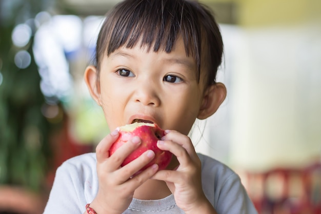 Happy asian child girl eating and biting an red apple. enjoy eating moment.