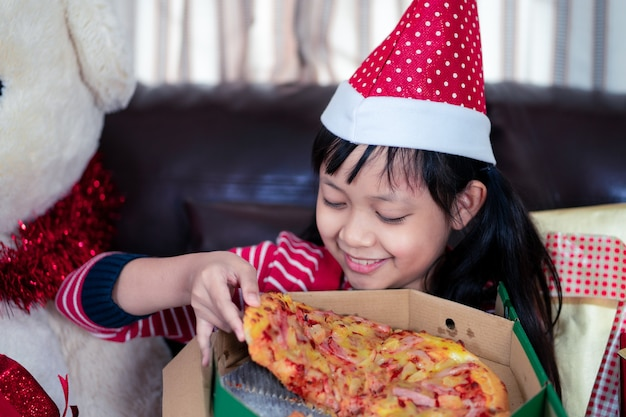 Happy asian child girl eating pizza in the room decorated for christmas