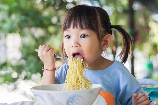 幸せなアジアの子供の女の子は一人でいくつかの麺を食べることを楽しんでいます。健康食品と子供のコンセプト。