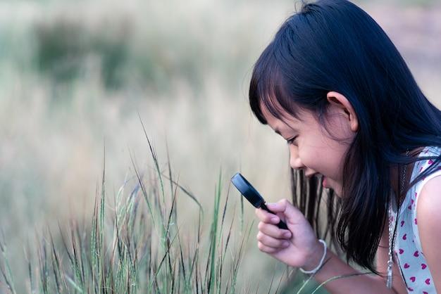 돋보기와 자연을 탐험하는 행복 한 아시아 아이 소녀.