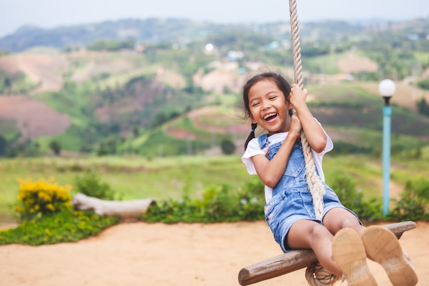 Happy asian child girl having fun to play on wooden swings in playground