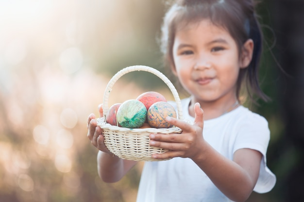 Happy asian child girl holding basket with colorful easter eggs