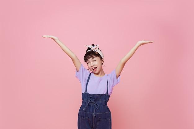 분홍색 배경에 고립 된 행복 한 아시아 아이 소녀.