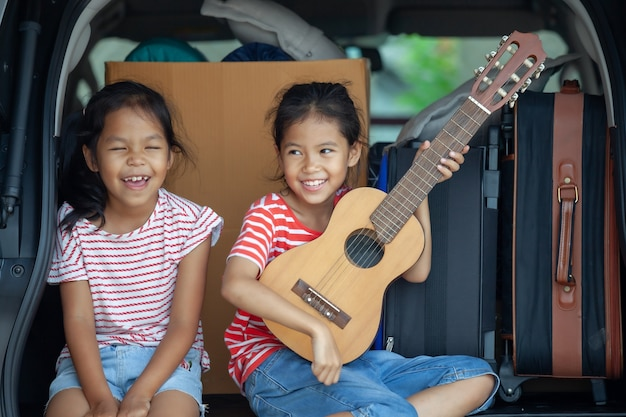 Happy asian child girl playing guitar and singing a song with her sister in a car trunk