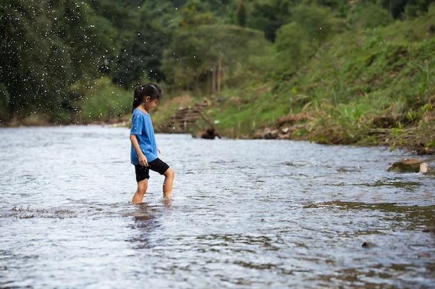 Счастливая азиатская детская девочка, играющая в реке с удовольствием и наслаждающаяся природой