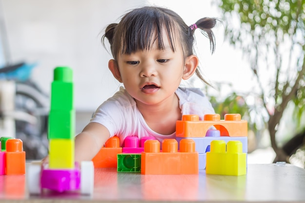 Happy asian child girl playing the plastic block toys. learning and education concept. smiling little baby.