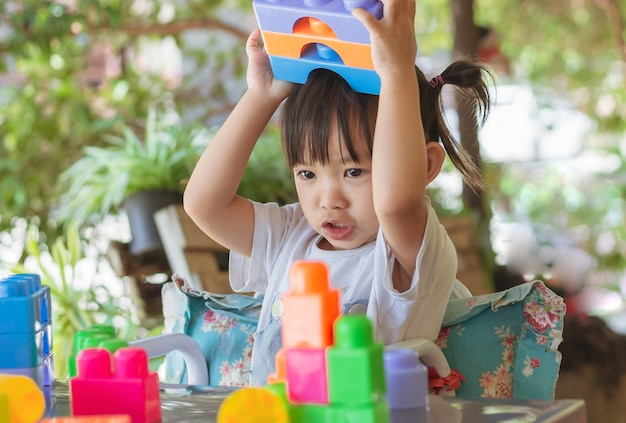Happy asian child girl playing the plastic block toys learning and education