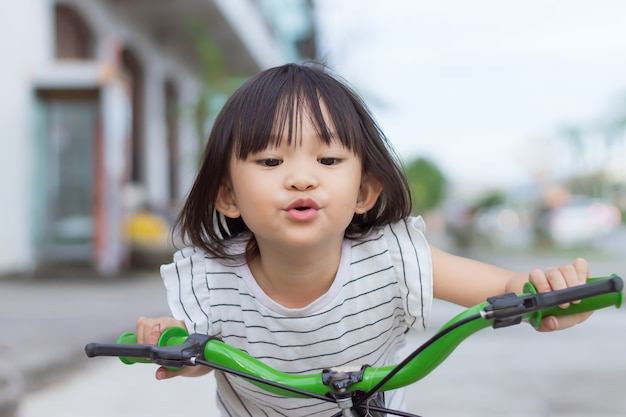 Happy asian child girl ride a bike at the park outdoor exercise for health and sport