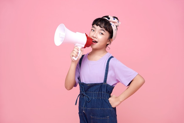 Happy asian child girl shouting into megaphone making announcement in isolated on pink background.
