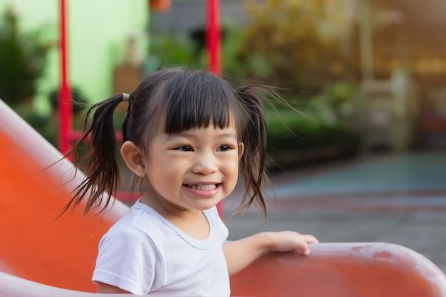 웃 고 웃 고 행복 한 아시아 아이 소녀. 그녀는 놀이터에서 슬라이더 바 장난감을 가지고 놀고 있습니다. 학습 및 어린이 개념의 활동.