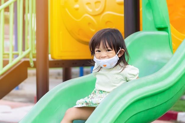 웃 고 패브릭 마스크를 쓰고 행복 한 아시아 아이 소녀. 그녀는 놀이터에서 슬라이더 바 장난감을 가지고 노는.