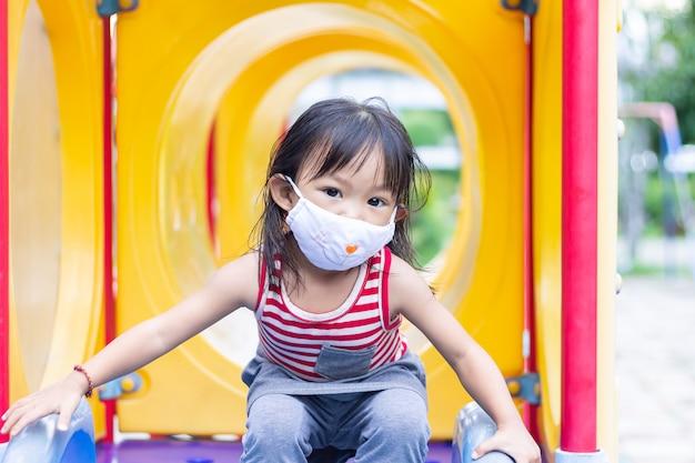 Счастливая азиатская девушка ребенка усмехаясь и нося маску ткани, она играя с игрушкой ползунка на спортивной площадке,